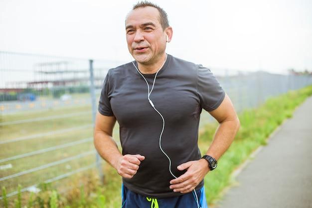 街でジョギングをしている中年の男性。年配の男性は、スポーツをして健康的でアクティブなライフスタイルをリードしています。