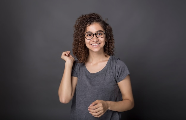 スタジオで黒の背景に笑みを浮かべてインドの若い女性の肖像画。毛むくじゃらの髪型と幸せなアフリカ系アメリカ人の女の子。