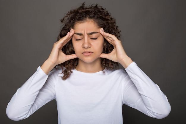 若いインド人女性が頭を痛めています。疲労または発熱による少女のこめかみの痛み。