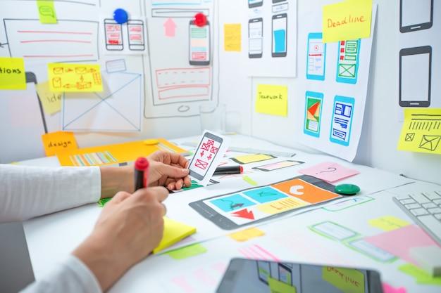 Веб-дизайнер разрабатывает приложение для мобильных телефонов. создание макета интерфейса пользователя функций смартфонов.