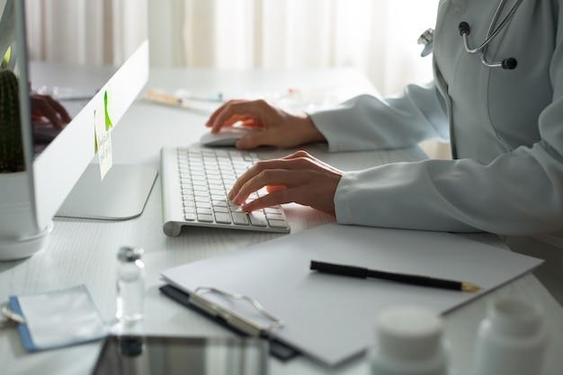 クリニックのテーブルでコンピューターに取り組んでいる医者の手。