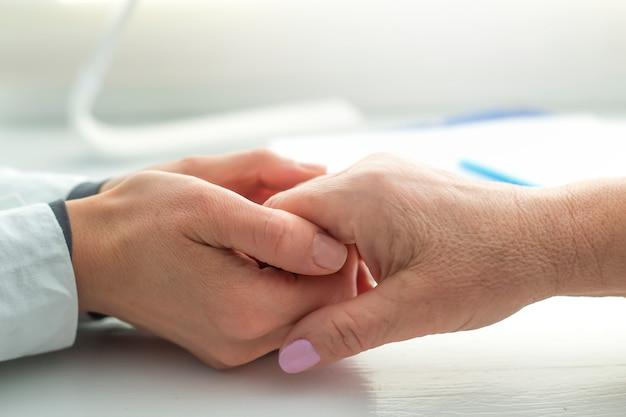 若い医者の手は、サポートの兆候として高齢の患者の女性の手を握っています。