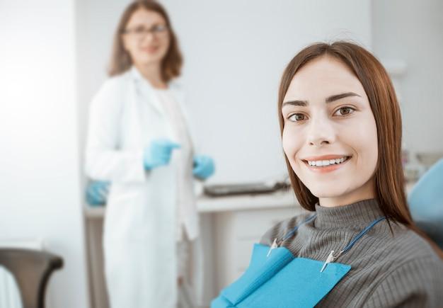 若い女性は、歯科用の椅子に座って健康な白い歯と笑顔、