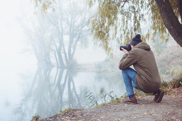 Молодой человек с фотоаппаратом фотографирует осеннюю природу во время путешествия.