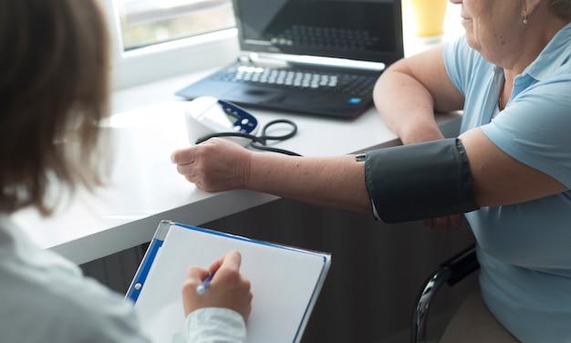 医者は年配の女性の圧力を測定します