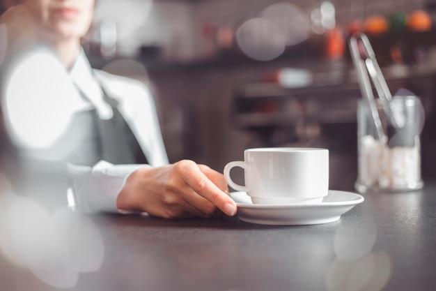 Женщина-официантка подает чашку кофе клиенту в кафе