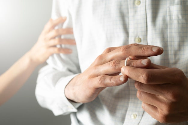 Понятие об измене. мужчина изменяет своей жене, снимая обручальное кольцо.