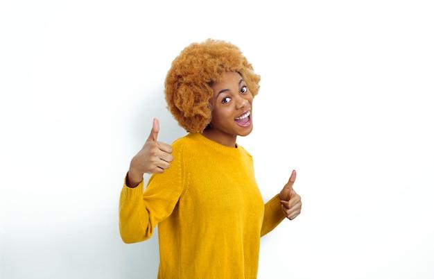 Портрет усмехаясь афро-американской молодой женщины показывая большие пальцы руки вверх.