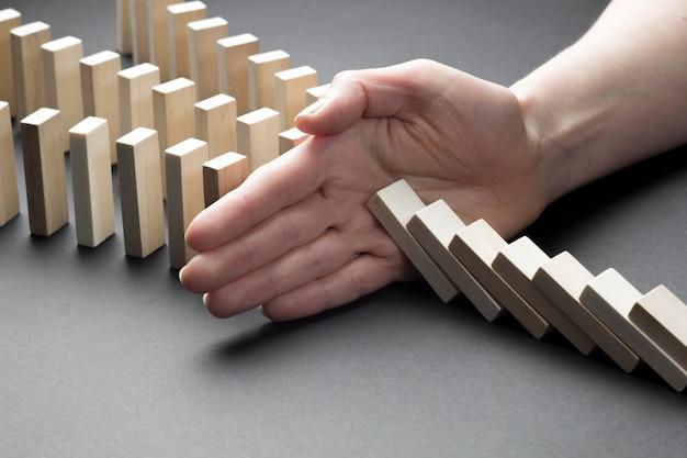 ビジネスマンはドミノを継続的に転倒またはリスクを停止します。ビジネスにおける戦略。
