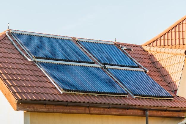 真空コレクター - 家の赤い屋根の太陽熱温水暖房システム