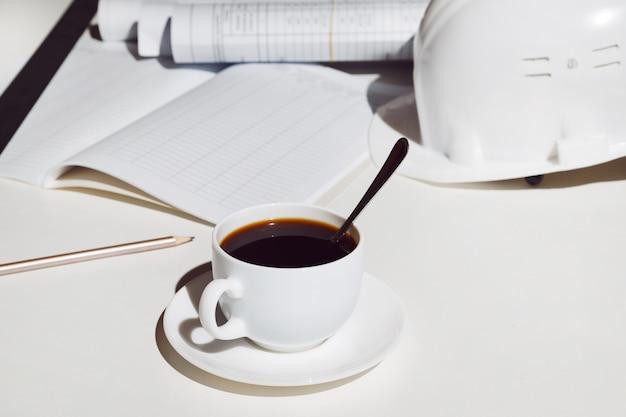 職場の建築家です。一杯のコーヒー、ヘルメット、白いテーブルの上の青写真。