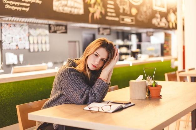 勤勉な日後のカフェに座っている若い女性フリーランサー。