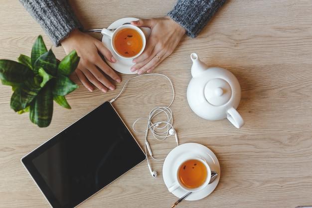 Девушка сидит за столом и пьет зеленый чай. вид сверху