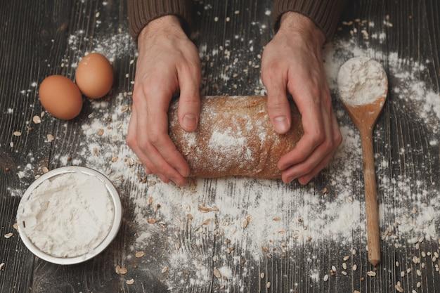 小麦粉と黒のパンに男性の手のクローズアップ。ベーキングとパティスリーのコンセプトです。