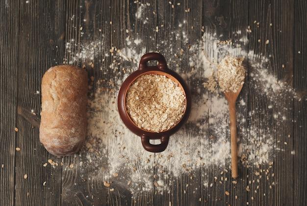 スプーンシリアルと素朴な背景の上のパン鍋。上からの眺め。