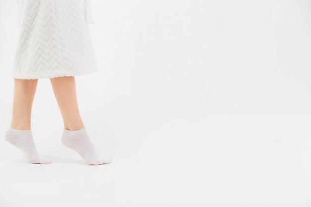 シャワーを浴びた後、白いバスローブと靴下を着た女の子が靴下を履きます。美しい女性の細い足のクローズアップ。側面図。