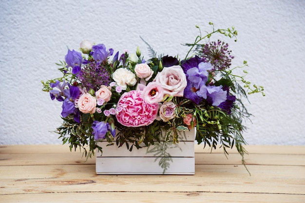 素朴なテーブルの上の木箱で牡丹の美しい柔らかい花束