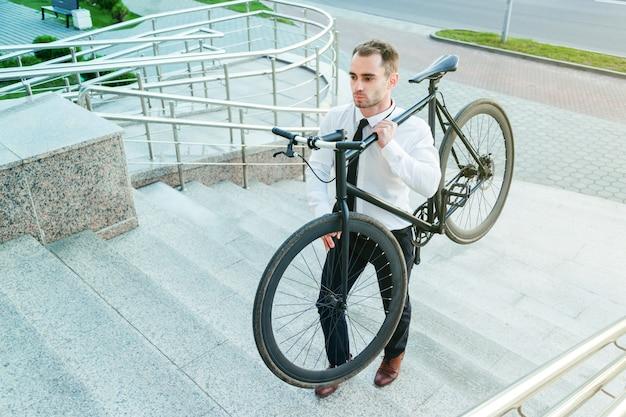 彼の自転車を運ぶビジネスマンは二階に行く