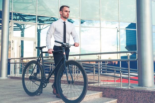 Человек в костюме, держа чашку кофе, шел по улице с его велосипед.