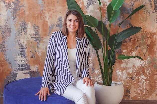 大きな植物の前でストライプジャックポーズの女性。屋内インテリアの肖像画。