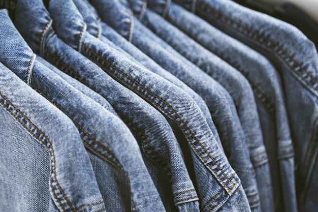 Модная джинсовая куртка на вешалках.