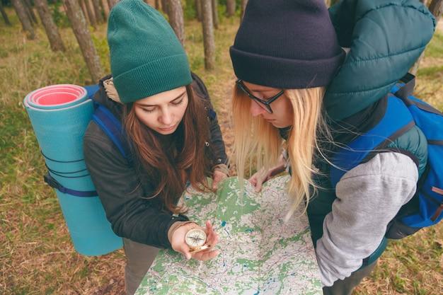 Два молодых туриста определяют маршрутную карту и компас