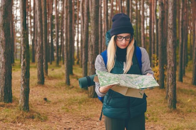 Красивая молодая женщина с картой путешествий и рюкзаком в сосновом лесу