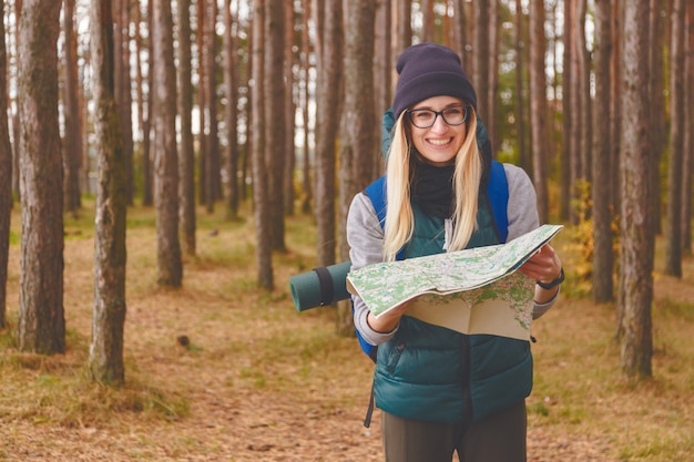 Улыбается молодая женщина с картой путешествий и рюкзак в сосновом лесу