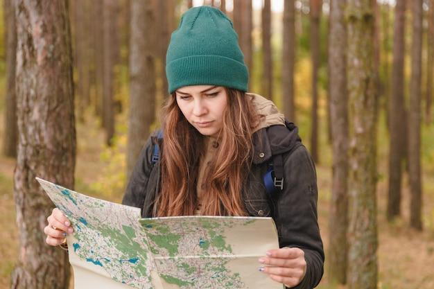 Женщина с картой путешествий и рюкзаком в сосновом лесу