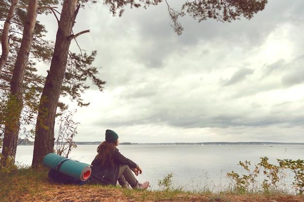 Путешествие одинокая женщина сидит возле лесного озера и смотрит далеко