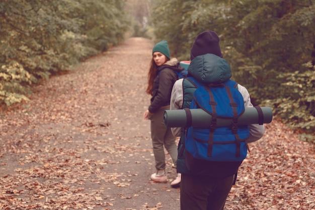 Подруги-путешественники с рюкзаками отправились в поход по лесу.