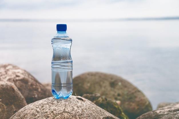 自然の風景の中の海の石の上の小さな水のボトル