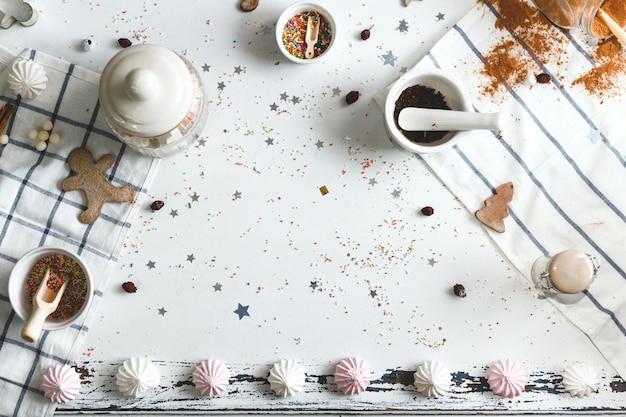 Белый стол с конфетной пудрой и различными праздничными сладостями вокруг центра