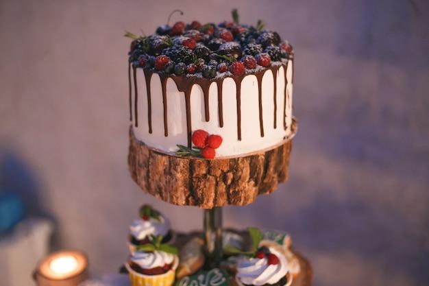 キャンドルライトの木製棚の上の果実とケーキとカップケーキ