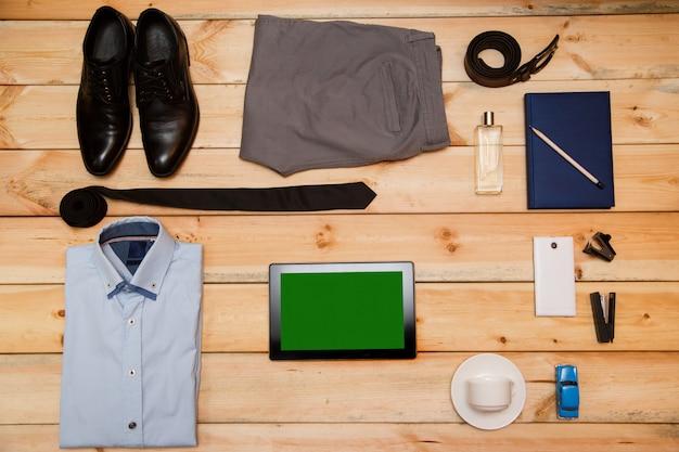 木製の背景に男の服やアクセサリーのセット