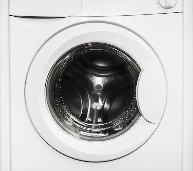 閉じたドアの空の洗濯機。