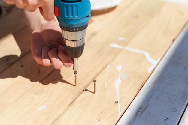 Человек закручивает винты в доски с помощью отвертки