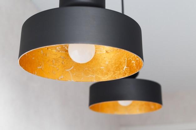 Два подвесных светильника из черного металла, украшенные золотой фольгой
