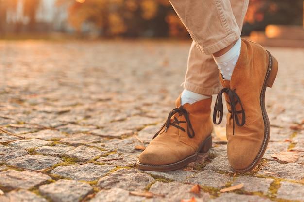 エレガントな秋のヌバックブーツの女性の足。市内の日没。