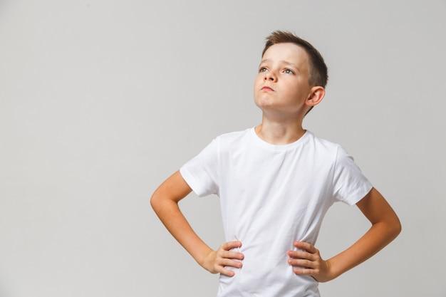 白い背景の上の彼の頭を持ち上げる彼の腰に手を持つ少年の肖像画