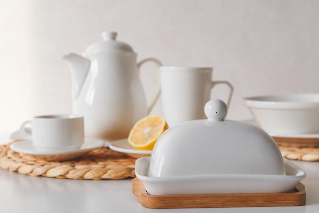 白いセラミック食器、繊維編組ラウンドプレースマット、カトラリーは、白い背景に設定します。北欧スタイル。