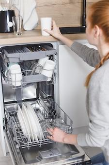 家事:食器洗い機に皿を置く若い女性