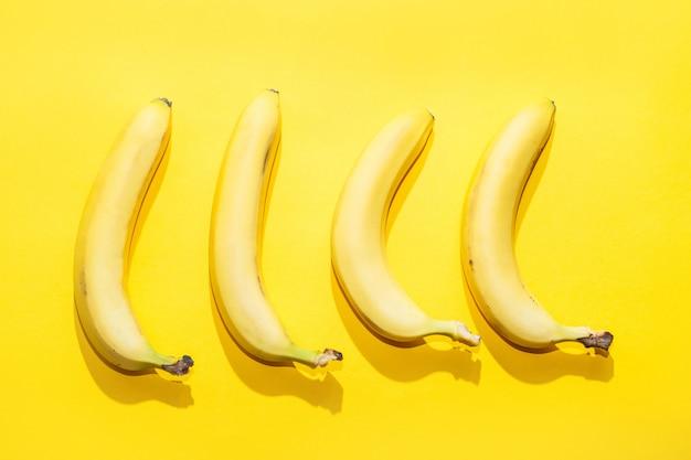 黄色のパステル調の背景にバナナ。最小限のアイデア食品のコンセプト