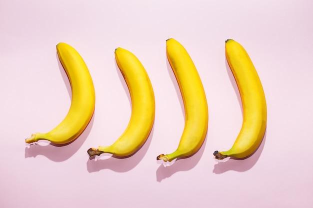 ピンクのパステル調の背景にバナナ。最小限のアイデア食品のコンセプト