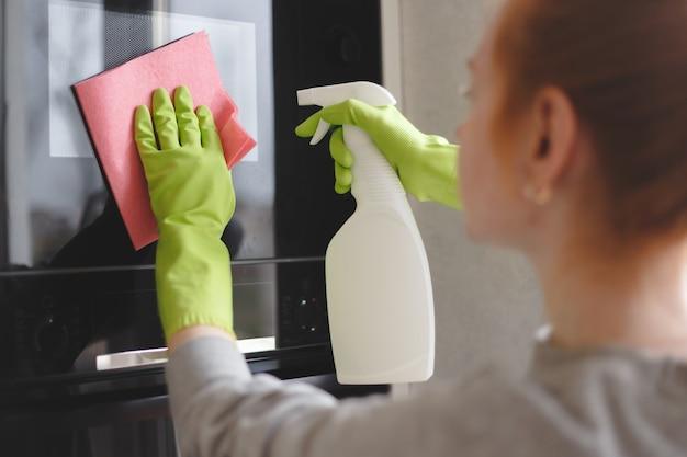 オーブンとキッチンの布で電子レンジのクリーニング女性をクローズアップ