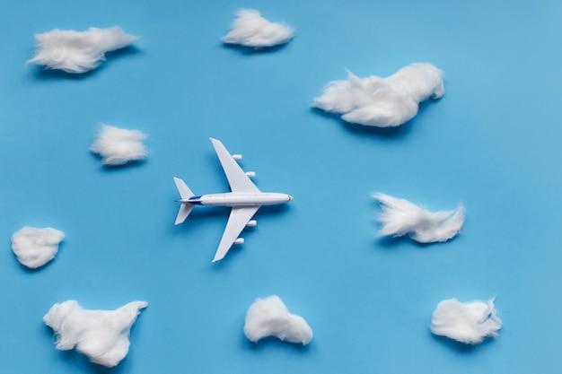飛行機と青の雲と旅行の概念のフラットレイアウトデザイン