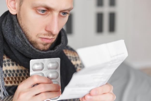 薬の医学的使用のための指示を読んで薬を持つ男。