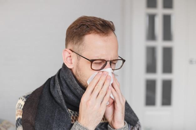 若い白人男が風邪をひいて鼻をかむ。