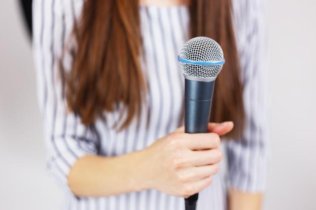 Микрофон в женской руке перед пением или публичным выступлением