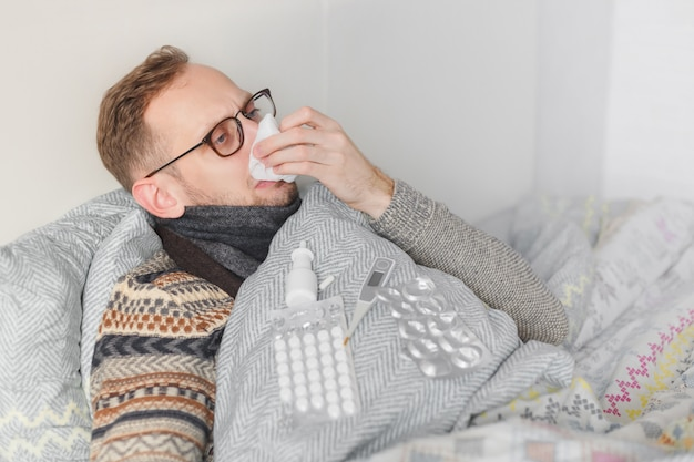 ベッドで病気に横たわっている間彼の鼻を吹く男